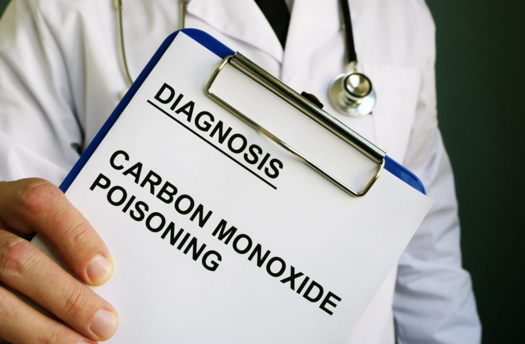 A doctor holding a clipboard with a piece of paper reading diagnosis carbon monoxide poisoning