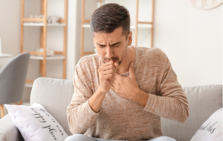 A man holding his chest coughing because of dry air