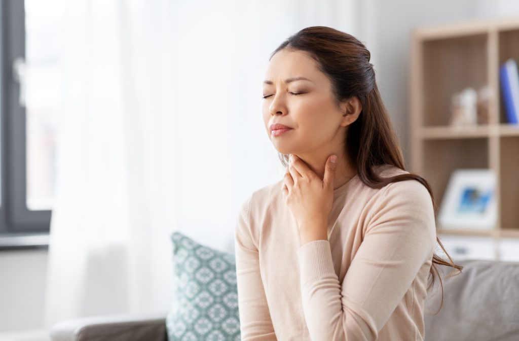 A woman suffering from a sore throat because of her air conditioning in her house not working properly