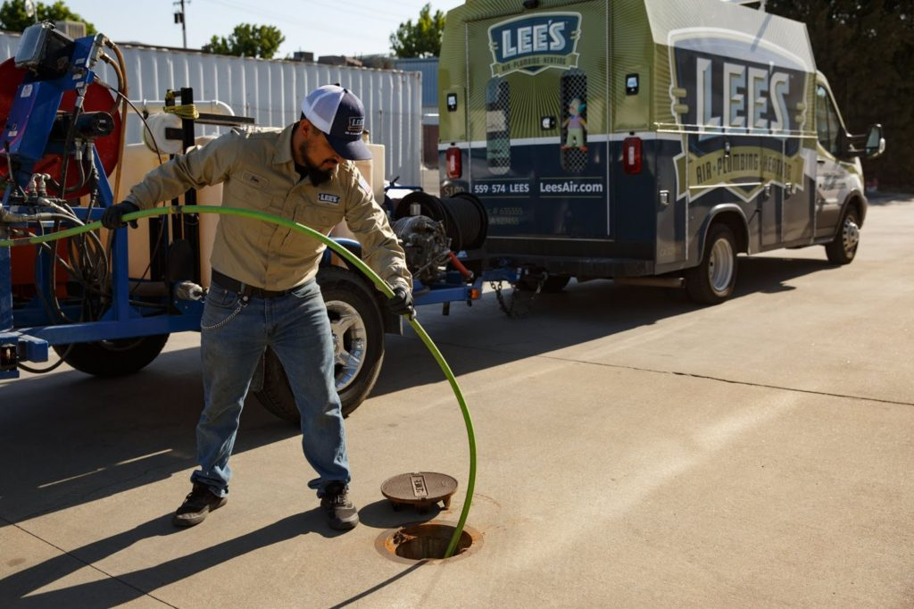 A plumber from Lee's Air, Pumbing, & Heating performing hydro jetting on a clogged drain