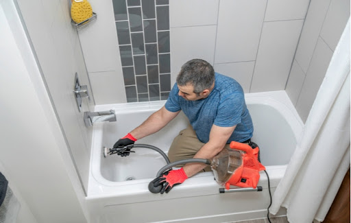 A plumber cleaning a bathtubs drain with a plumbers snake