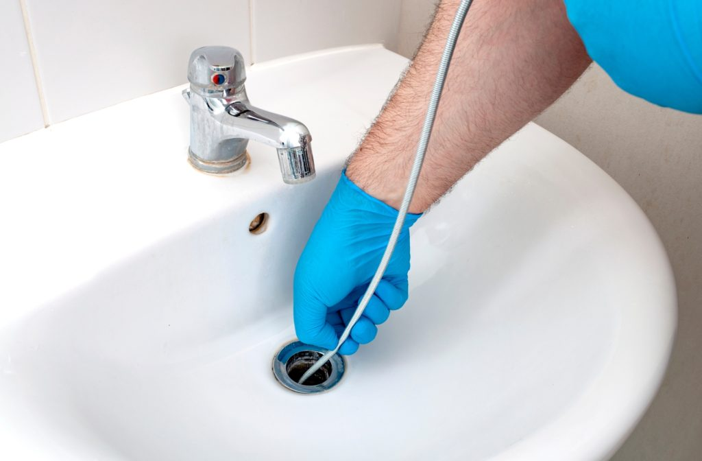 A plumber using a plumbing snake to unclog a drain